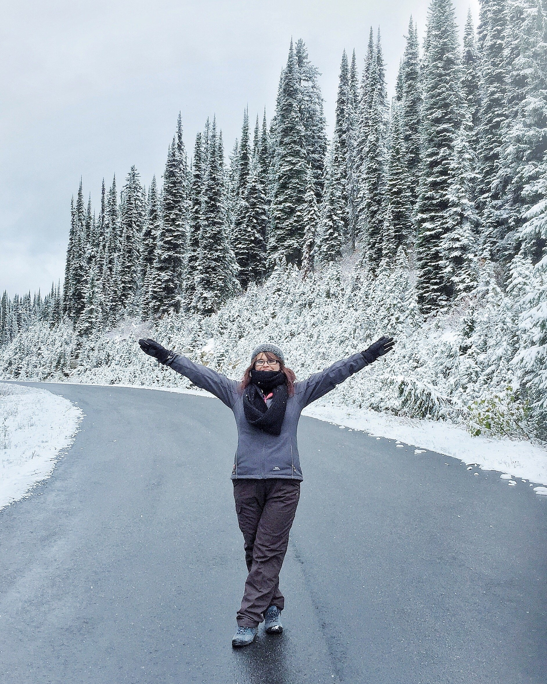 Blog Author dressed in all her winter clothes in the middle of a road on the road to Mount Revelstoke