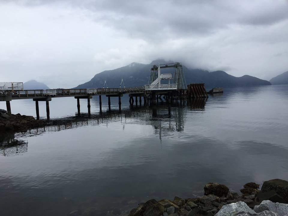 Clouds hang low over the mountains overlooking Howe Sound as a pier juts out into the water