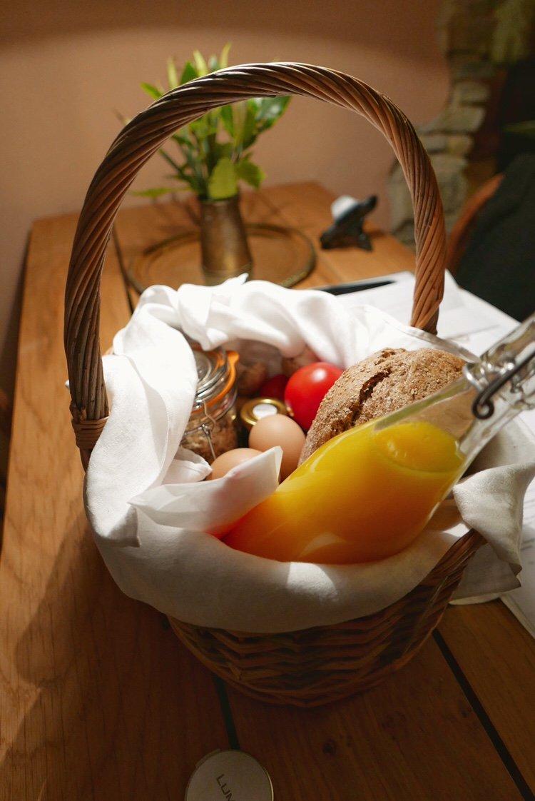 Breakfast basket full of eggs, tomatoes, bread, mushrooms, muesli, jam, bacon, mushrooms and orange juice