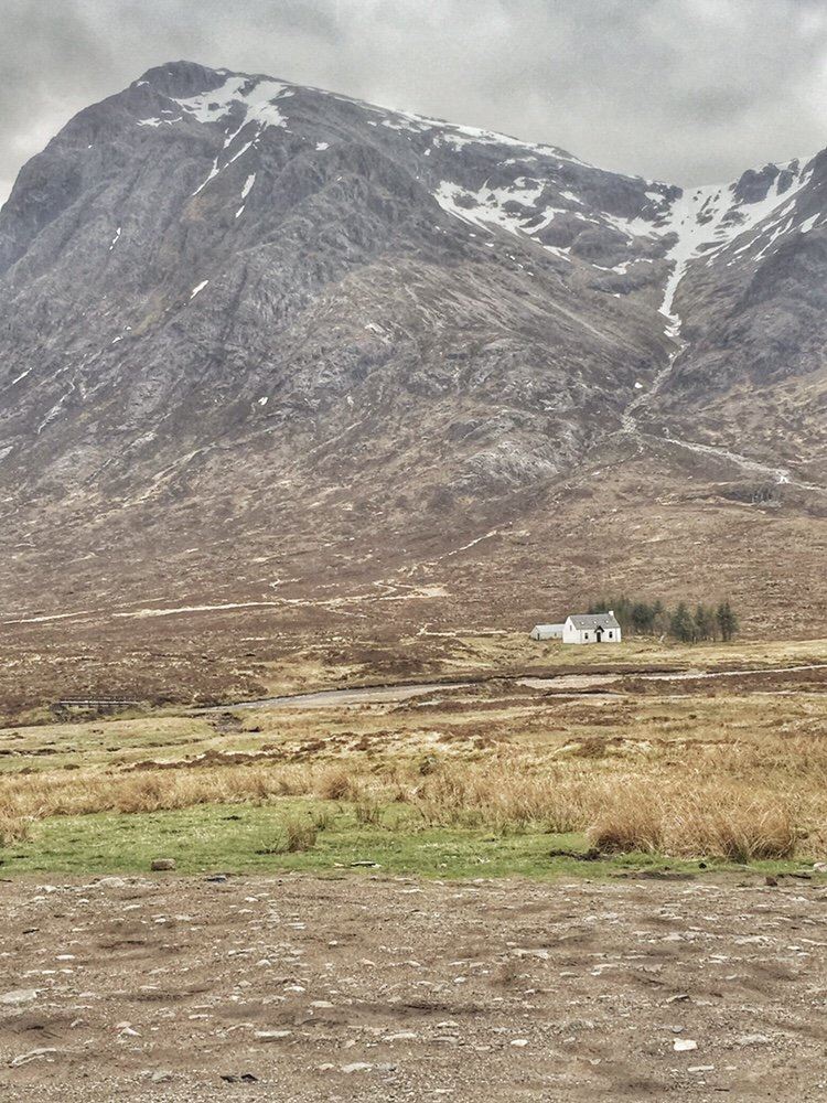 Small white farmhouse in front of mountain range in Scotland