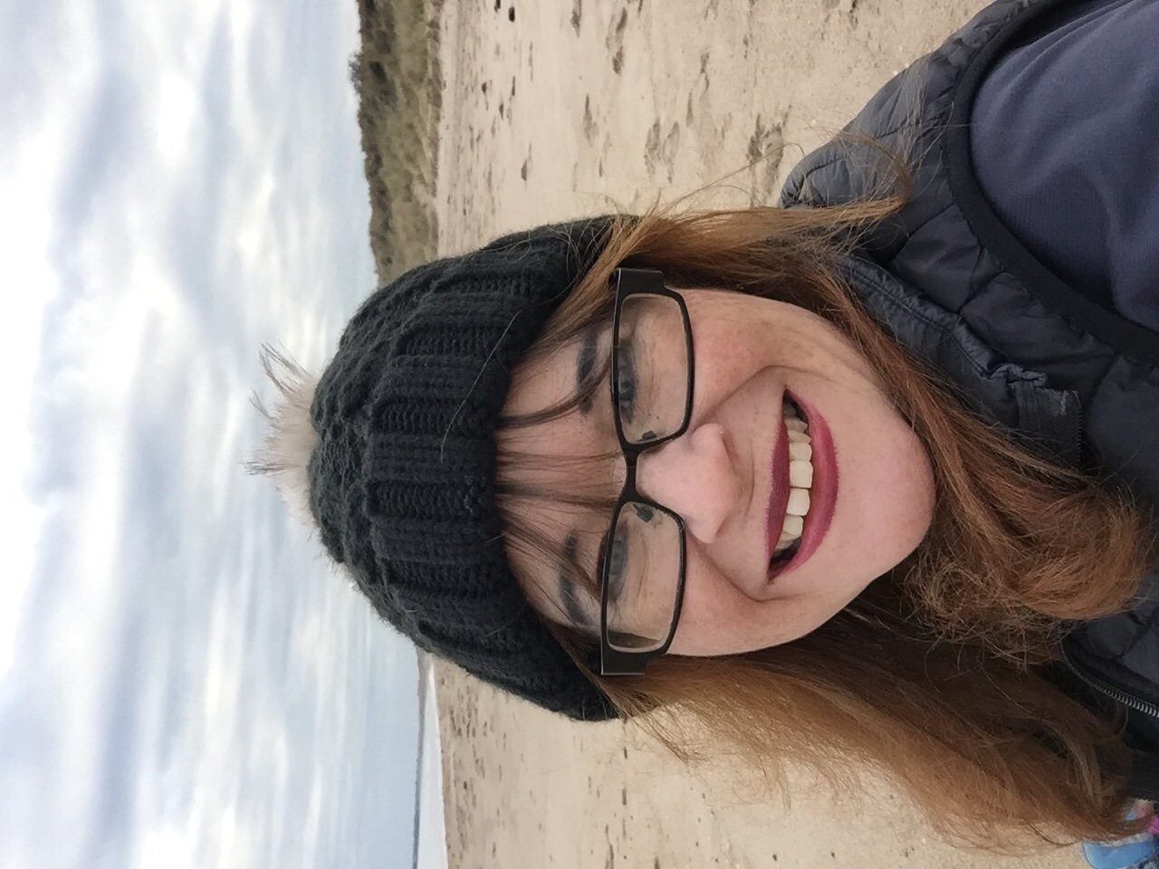 Hiking Amble to Alnmouth. Warkworth Beach. Woman on beach smiling in black woolly hat