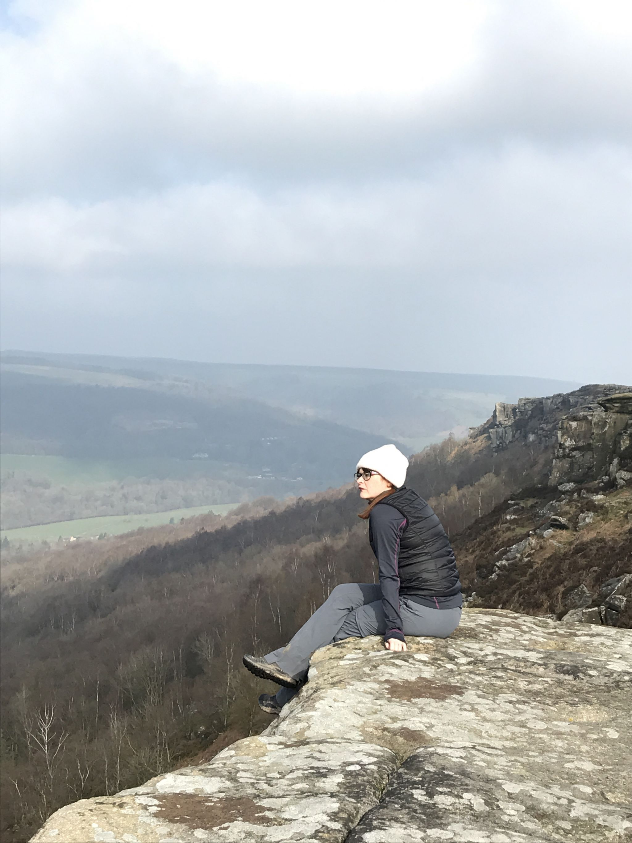 Woman sitting on edge of a rock in the Peak District