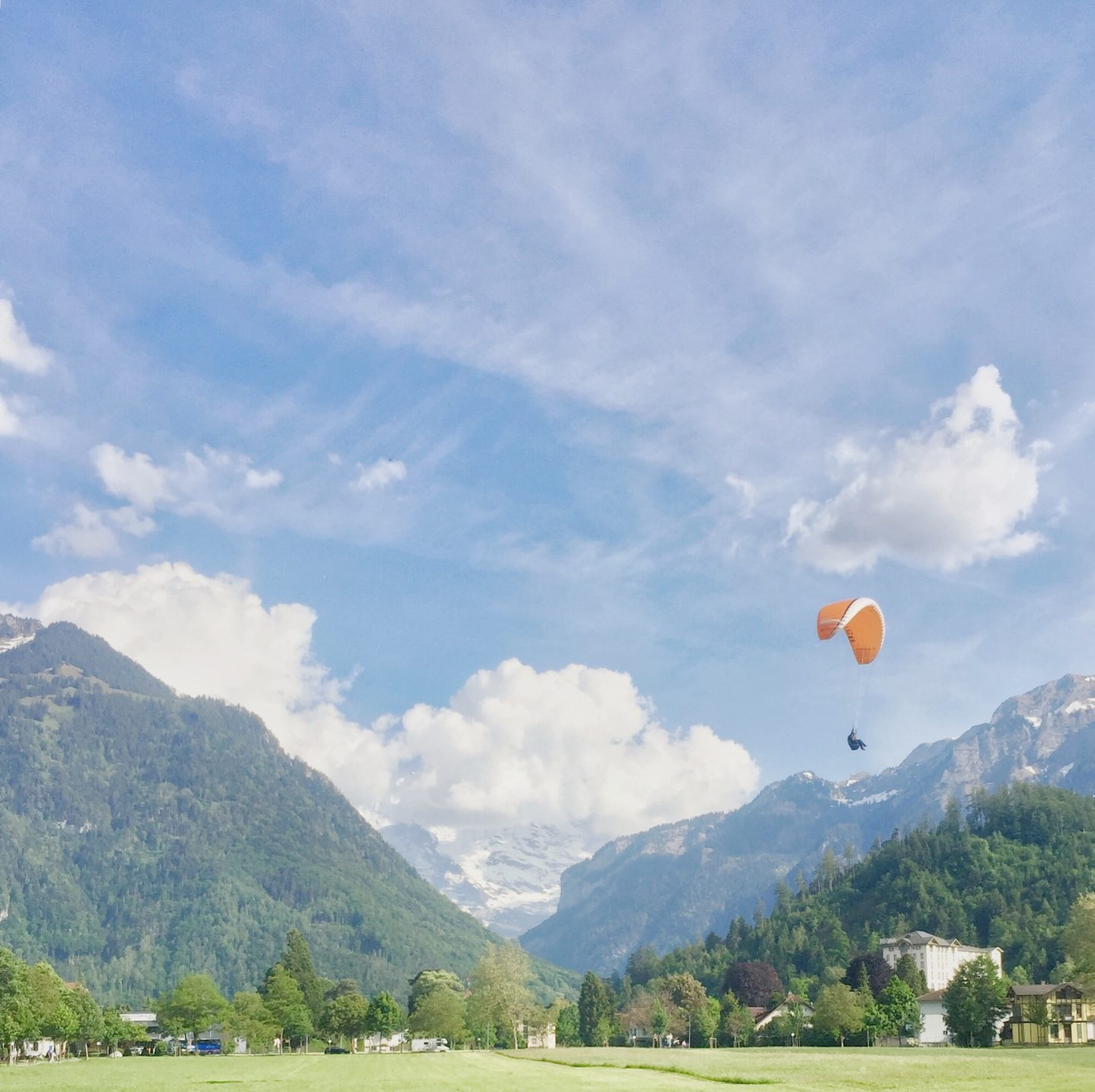 Paraglider descending with Swiss Alps in the background
