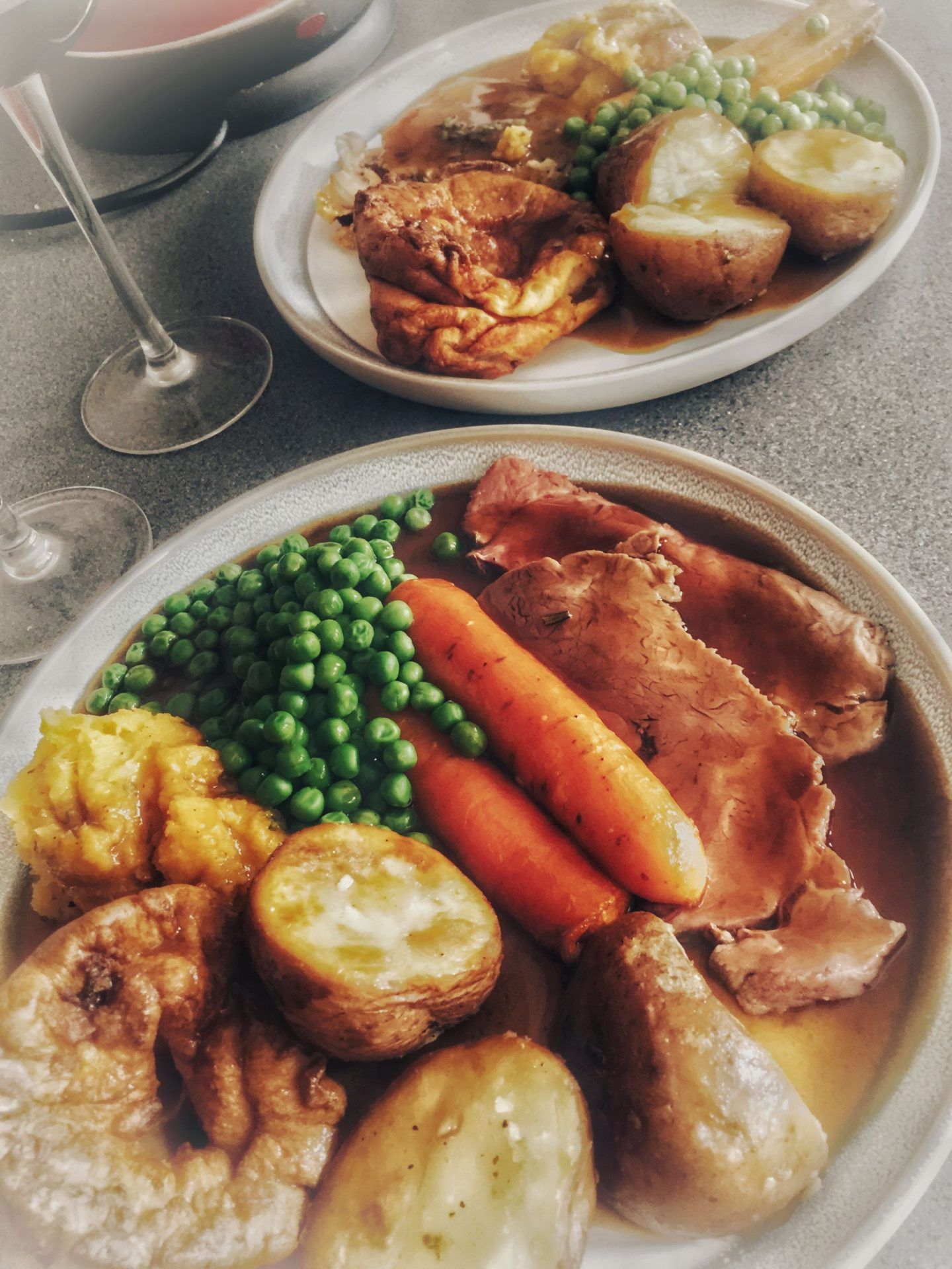 A Sunday roast, with beef, carrots, roast potatoes, peas and a glass of red wine