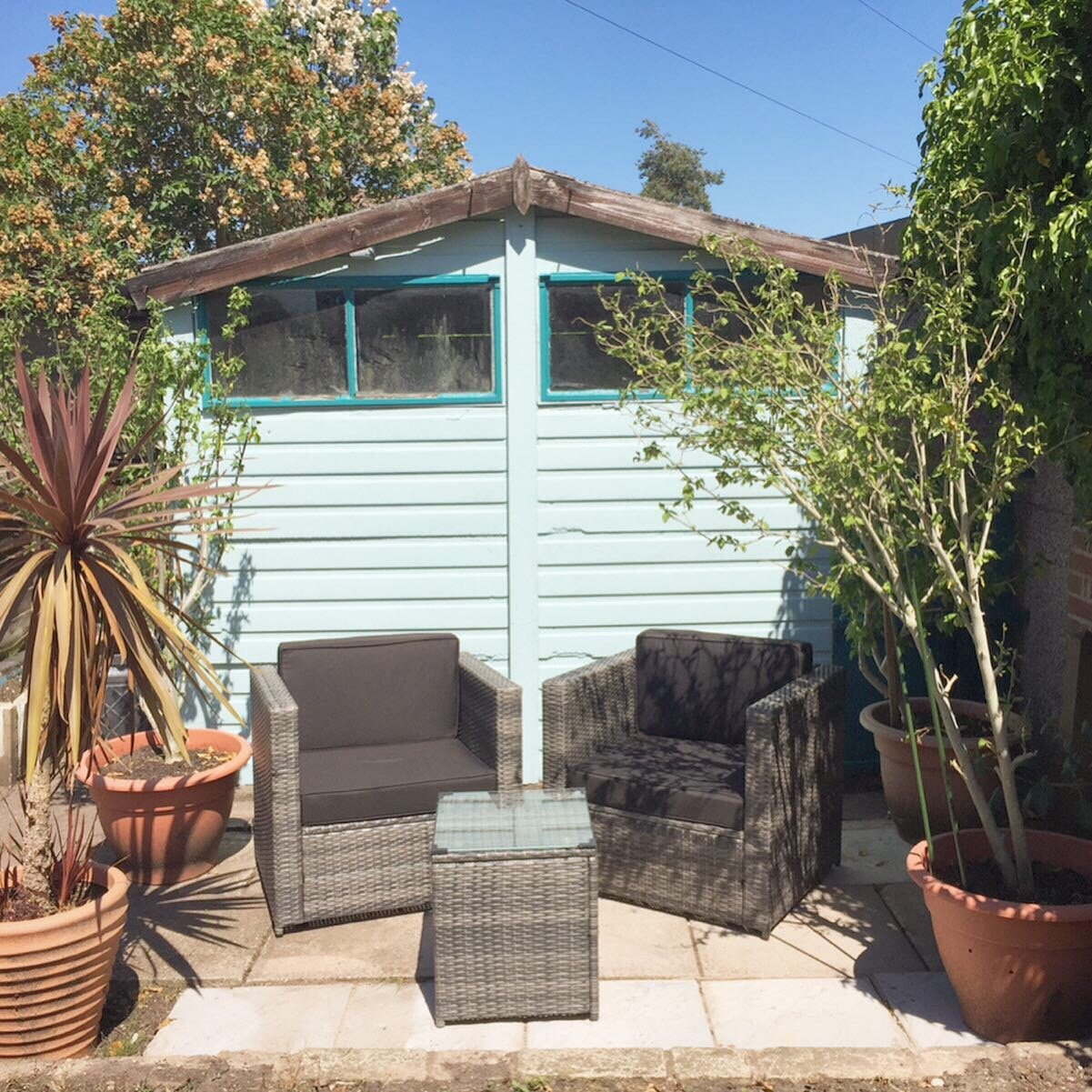 Two garden chairs and a table in front of a garden shed with potted trees