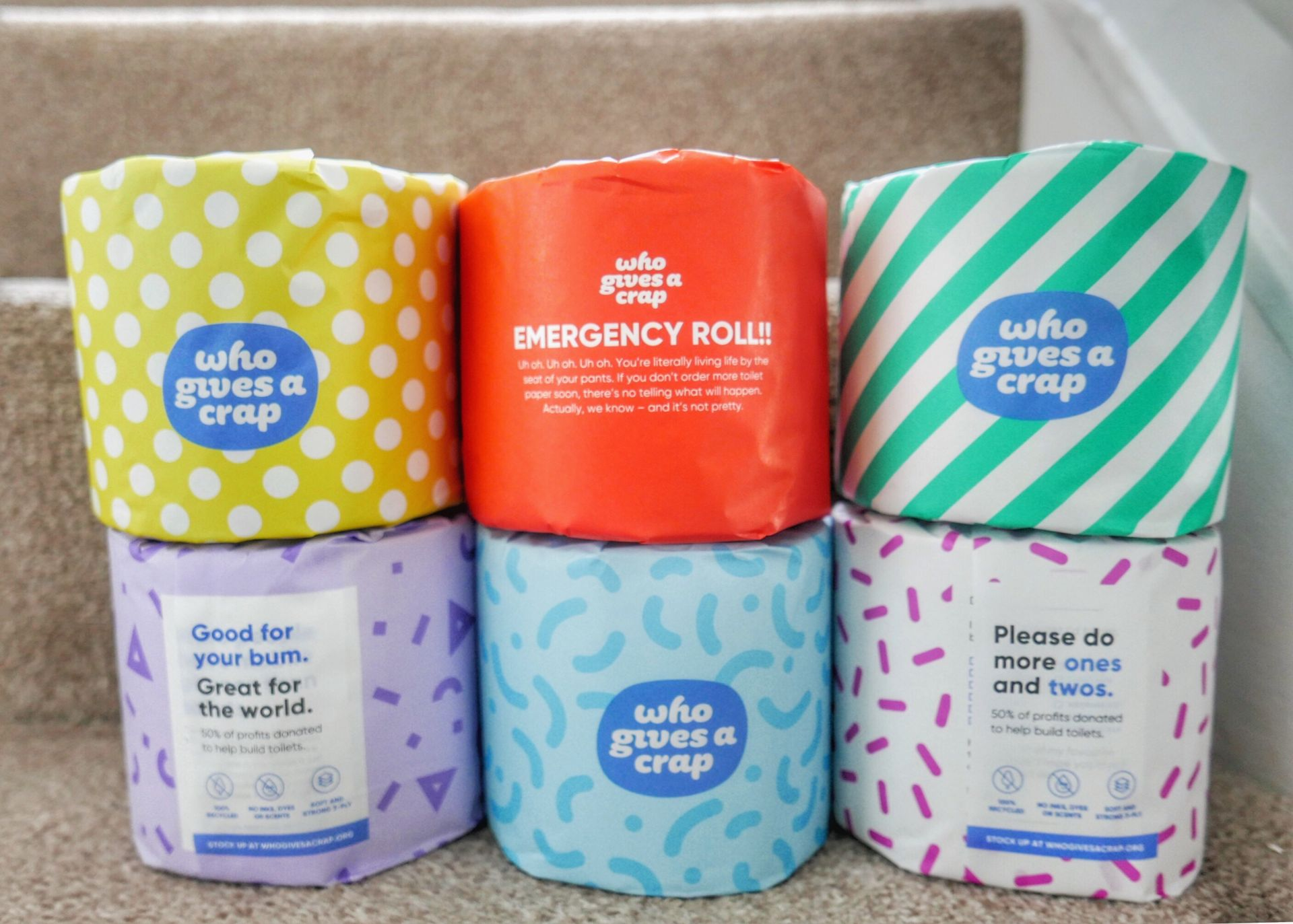 Six toilet rolls in brightly coloured paper