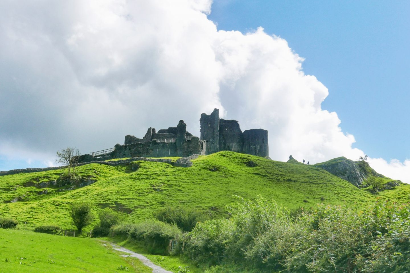 Cerreg Cennen castle in Wales sitting on a steep green slope